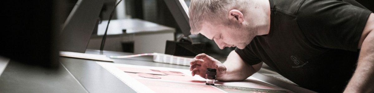 Strandbygaard Trykkeri medarbejder laver kvalitetstjek i trykkeri og prepress