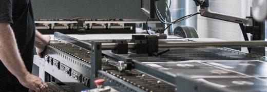 Strandbygaard Trykkeri viser medarbejder der arbejde ved trykmaskine i trykkeri