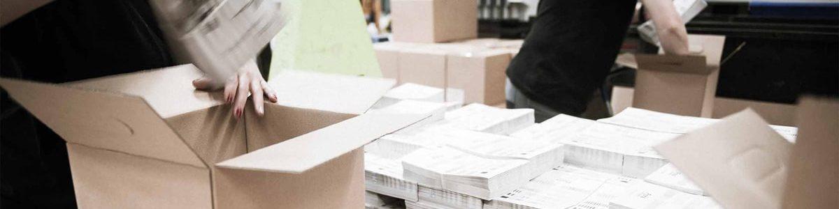 Strandbygaard Trykkeri viser medarbejdere der arbejder i pakkeriet og gør tryksager klar til forsendelse