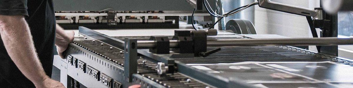 Medarbejder hos Strandbygaard Grafisk arbejder på en trykmaskine